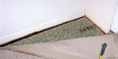 Photo of carpet pulled back showing water damage.