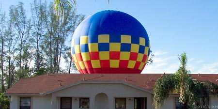 Hot air balloon behind condo building.